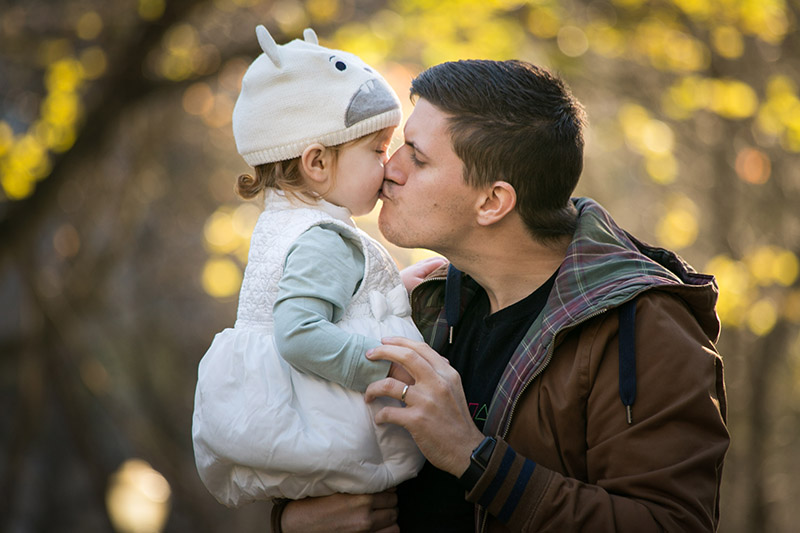 Father and daughter with autumn leaves